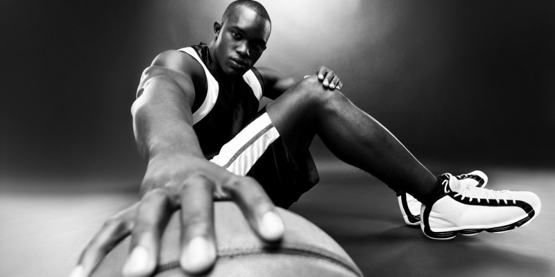 Successful young basketball player sitting with a ball